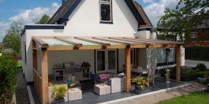 houten overkapping met glazen dak aan woonhuis